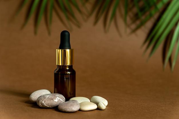 Ciemna szklana butelka z zakraplaczem z pipetą lub kroplami. mock up essential liquid. modne tło tropikalne liście i kamienie morskie.