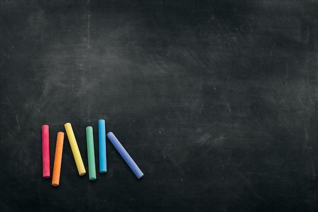 Ciemna tablica z kolorowymi kredkami do rysowania