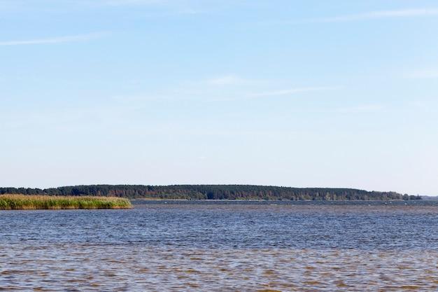 Ciemna woda w dużym jeziorze, letni krajobraz z błękitnym niebem