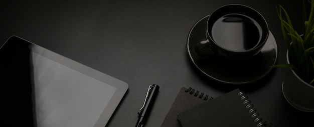 Ciemne biurko z cyfrowym tabletem, papeterią, długopisem, filiżanką kawy i miejscem do kopiowania