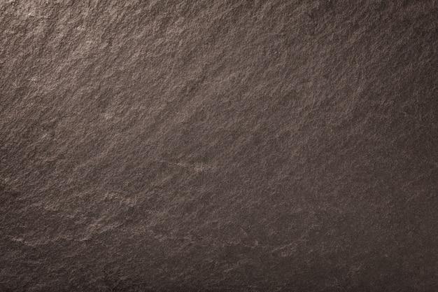 Ciemne brązowe tło z naturalnego łupka. tekstura brązowego kamienia zbliżenie. makro grafitowe tło