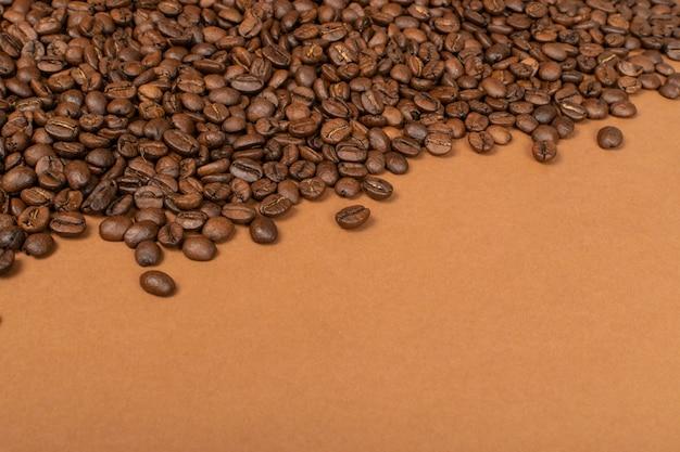 Ciemne całe ziarna kawy na brązowym tle z copyspace.