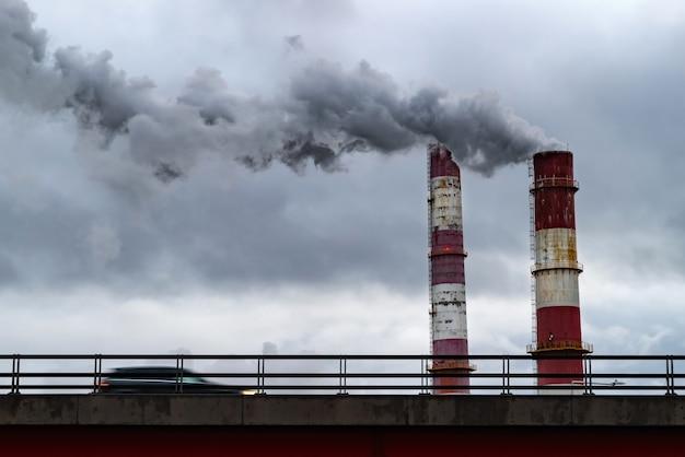 Ciemne chmury dymu wydobywające się z komina fabrycznego