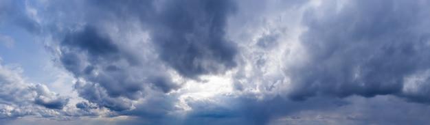 Ciemne chmury na tle błękitnego nieba z prześwitującymi promieniami słońca. panorama nieba.