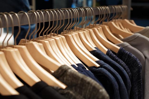 Ciemne damskie ubrania na drewnianych wieszakach na stojaku w sklepie z modą