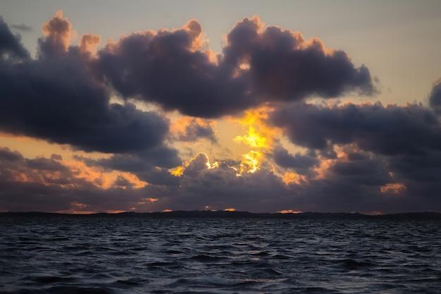 Ciemne, dramatyczne chmury zachodzącego słońca nad wodą morską.