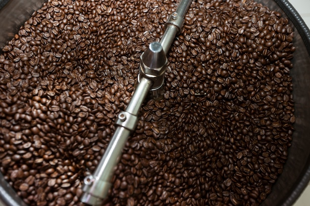 Ciemne i aromatyczne ziarna kawy w nowoczesnej maszynie do prażenia