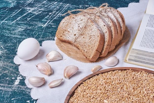 Ciemne kromki chleba z jajkami i czosnkiem na niebieskim stole.