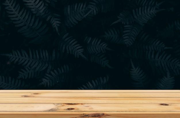 Ciemne liście tło z gładkim drewnianym stołem produktowym