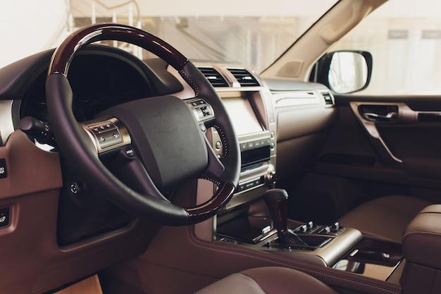 Ciemne luksusowe wnętrze samochodu - kierownica, dźwignia zmiany biegów i deska rozdzielcza.