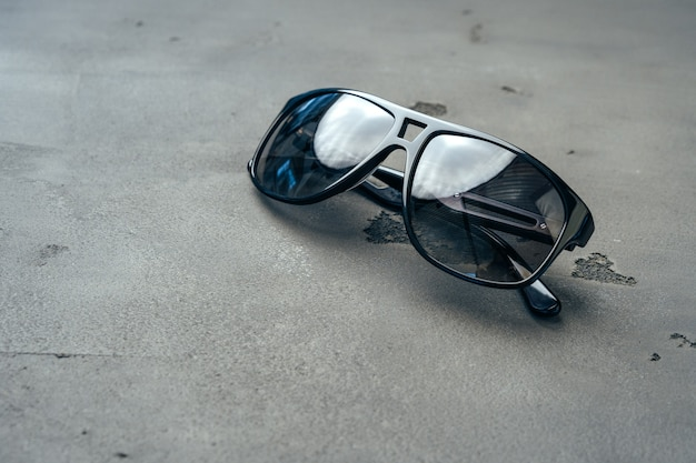 Ciemne męskie okulary przeciwsłoneczne na szarym betonie