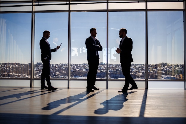 Ciemne męskie sylwetki na tle panoramicznego okna. biznesmeni płci męskiej wyglądający przez duże okno wieżowca z widokiem na metropolię