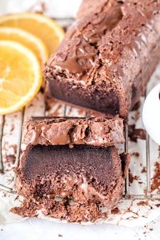 Ciemne, mokre ciasto czekoladowe, z chrupiącą skórką, kroplami, okruchami, metalowymi tabliczkami, dwuczęściowym ciastem, kółeczkami pomarańczowymi, białym tłem, pionowymi.