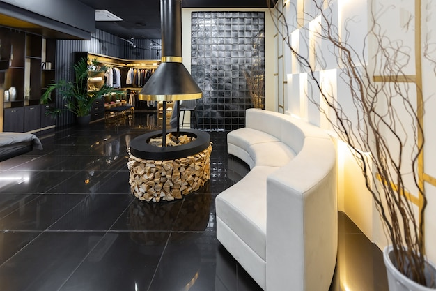 Ciemne nowoczesne stylowe męskie wnętrze mieszkania z oświetleniem, ozdobnymi ścianami, kominkiem, garderobą i ogromnym oknem