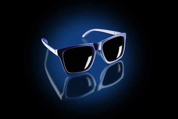 Ciemne okulary przeciwsłoneczne w kręgu niebieskiego światła na czarnej odblaskowej powierzchni.