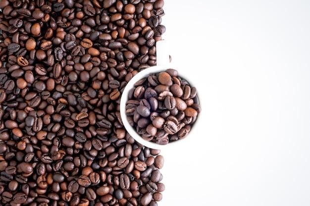 Ciemne palone ziarna kawy i białe tło filiżanki, widok z góry