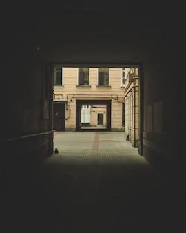 Ciemne przejście z widocznym budynkiem w tle