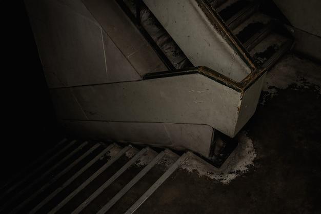 Ciemne światło brudnych schodów w starym budynku.