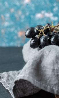 Ciemne świeże winogrona w koszu na kolorowym