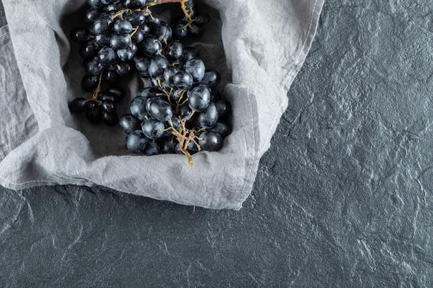 Ciemne świeże winogrona w koszu na szarym obrusie.