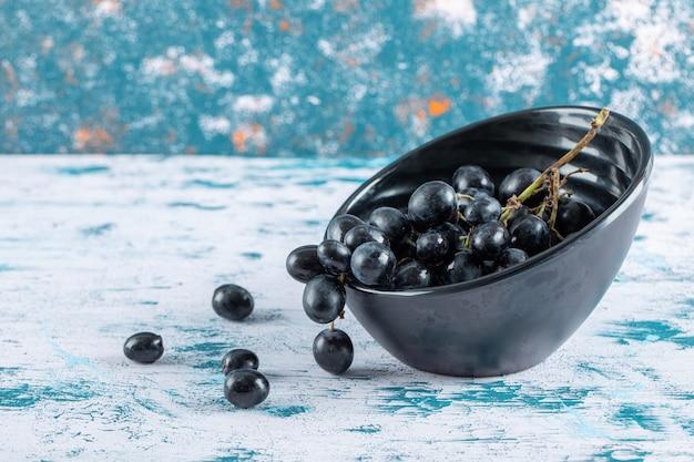 Ciemne świeże winogrona w misce na kolorowym