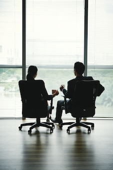 Ciemne sylwetki mężczyzny i kobiety siedzącej z kubkami w krzesłach biurowych przed oknem