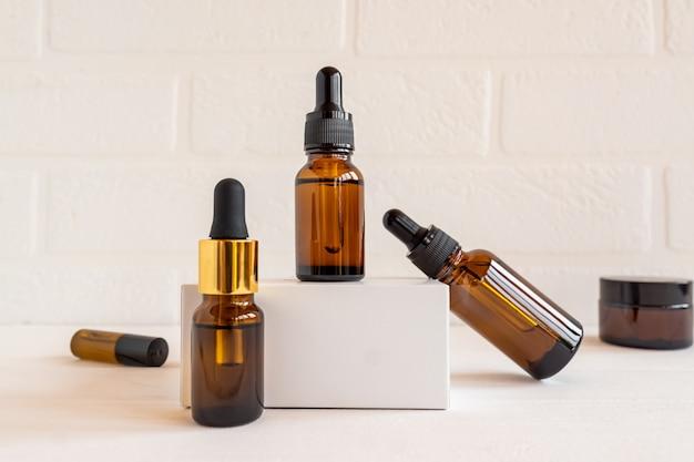 Ciemne szklane i przezroczyste butelki kosmetyczne z serum do twarzy lub olejkiem eterycznym na białym tle. produkty kosmetyczne unbradned beauty.