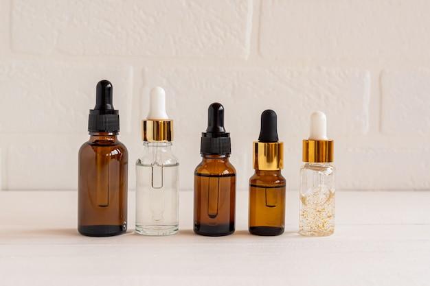 Ciemne szklane i przezroczyste butelki kosmetyczne z serum do twarzy lub olejkiem eterycznym na drewnianym tle. produkty kosmetyczne unbradned beauty.