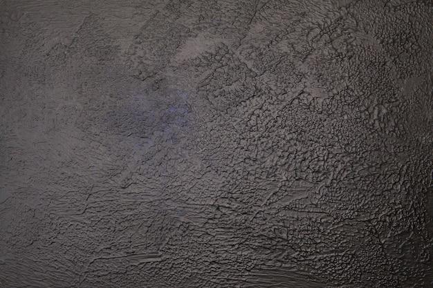 Ciemne teksturowane tło betonu z plamą jasnego i niebieskiego odcienia