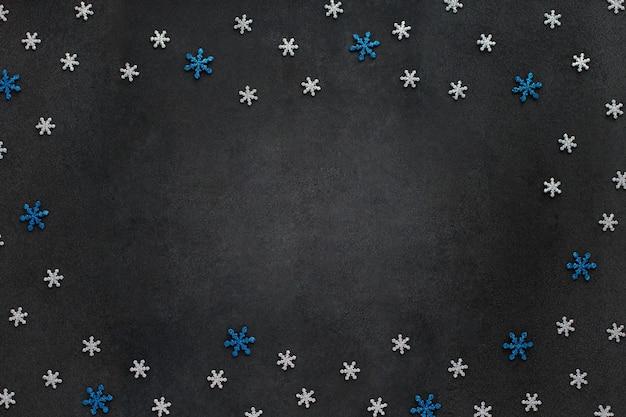 Ciemne tło z ciętym brokatem srebrnym i niebieskim płatkami śniegu.