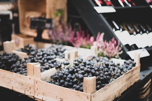 Ciemne winogrona w drewnianym pudełku na ladzie sklepowej. wino w tle. kreatywny handel, rozwiązania dekoracyjne.