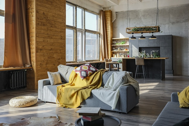 Ciemne wnętrze dużego przytulnego wiejskiego domu w stylu loftu. mieszkanie na planie otwartym z aneksem kuchennym, strefą wypoczynku i sypialnią. ogromne okna i drewniana dekoracja