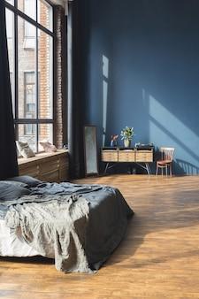 Ciemne wnętrze nowoczesnego, stylowego, dużego apartamentu typu studio w stylu loftu na planie otwartym z kolumnami i wysokimi sufitami.