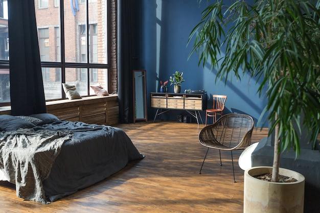 Ciemne wnętrze nowoczesnego, stylowego, ogromnego apartamentu typu studio w stylu loftu na planie otwartym z kolumnami i wysokim sufitem
