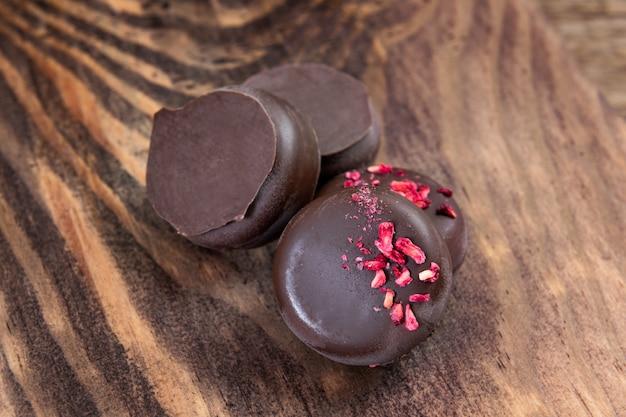 Ciemni czekoladowi cukierki na drewnianym tle