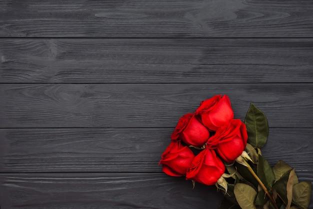Ciemno czerwone róże na drewnianej powierzchni