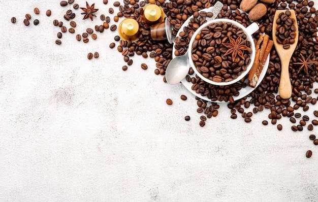 Ciemno palone ziarna kawy i kapsułki z gałkami ustawionymi na białym betonie
