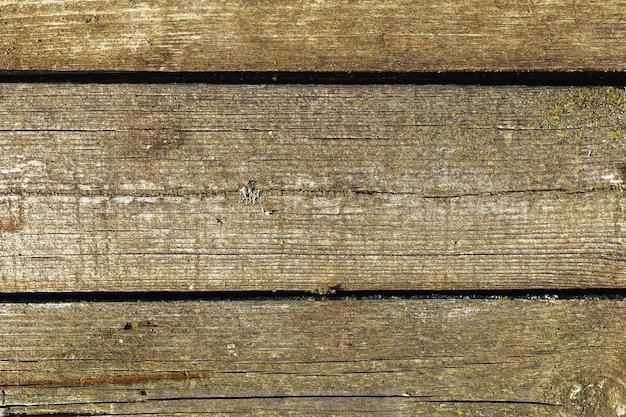 Ciemnobrązowa drewniana tekstura naturalnie starzejące się tło. deska stodoły zielony mech stara drewniana tekstura