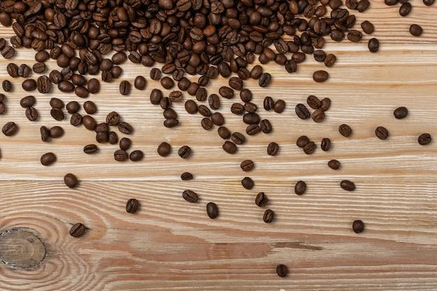 Ciemnobrązowe całe ziarna kawy na tle drewna z copyspace.