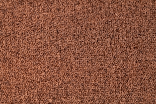 Ciemnobrązowe puszyste tło z miękkiej, welurowej tkaniny. tekstura tkaniny z wełny umbry