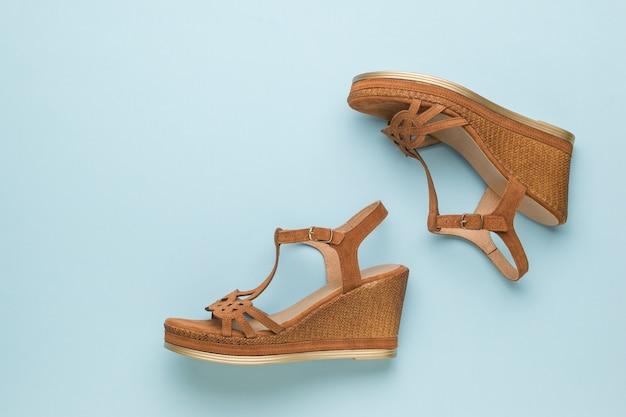 Ciemnobrązowe sandały damskie na niebieskim tle.