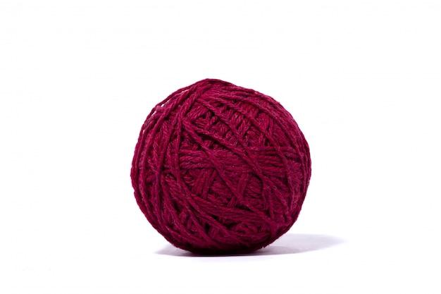 Ciemnoczerwona piłka wełniana nić, odosobniona biel ściana.