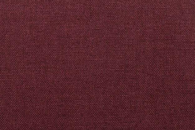 Ciemnoczerwone tło z materiału włókienniczego.