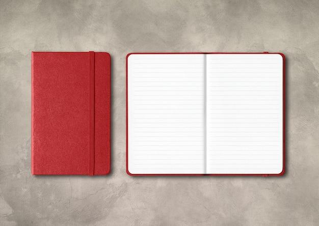 Ciemnoczerwony zamknięte i otwarte notebooki w linie na białym tle na tle betonu
