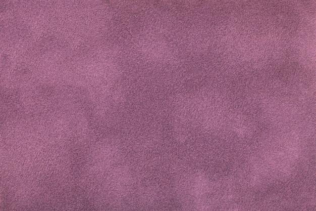Ciemnofioletowe matowe tło z zamszowej tkaniny. aksamitna tekstura bezszwowej liliowej tkaniny filcowej