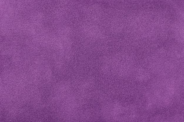 Ciemnofioletowe matowe tło zamszowej tkaniny, zbliżenie. aksamitna tekstura bezszwowej tkaniny lawendowej, makro. struktura fioletowego płótna z filcu.