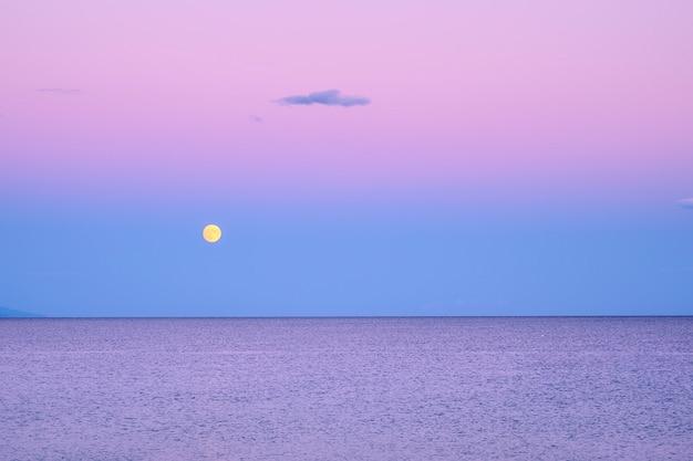 Ciemnofioletowe niebo z żółtym księżycem nad morzem po zachodzie słońca w grecji
