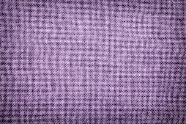 Ciemnofioletowe tło z materiału włókienniczego z wiklinowym wzorem, makro. tekstura liliowej tkaniny. lawendowe tło tkaniny z winietą.