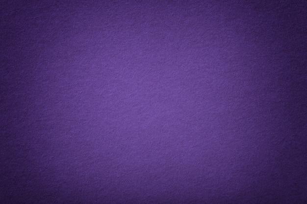 Ciemnofioletowy matowy zamszowy zbliżenie tkaniny. aksamitna faktura filcu.