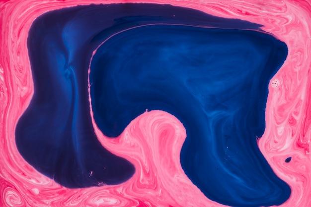 Ciemnoniebieska farba na tle mieszanej różowej tekstury